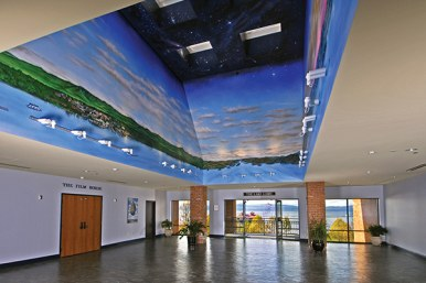 large lobby with stone floors and ceiling mural