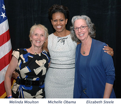 Three woman smiling, includes the first lady of the United States of America