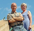 Ted Milks and Dottie Weinstein standing on a staircase below blue sky