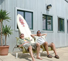 Dave Schmidt and Tom Pasley sitting in the sun in front of a surfboard