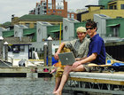 Mike McCarney and Ben Ipsen sitting on the pier with a laptop in front of main street landing