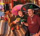 Jeanette and Jim Wood drinking margaritas and wearing sombreros