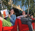 Nicole Ravlin and Ken Liatsos sitting in red chairs reading magazines