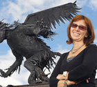Mira Niagolova in front of a large, black, winged creature